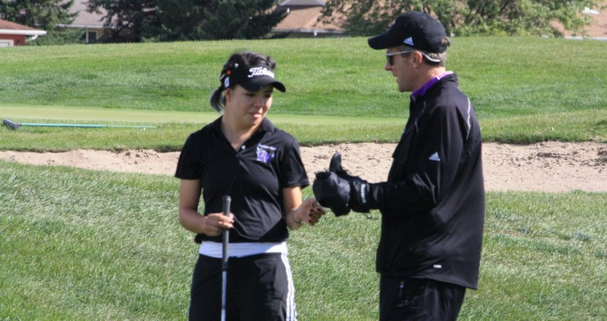 Head coach Mark Clouse giving one his golfers advice on which club to use.
